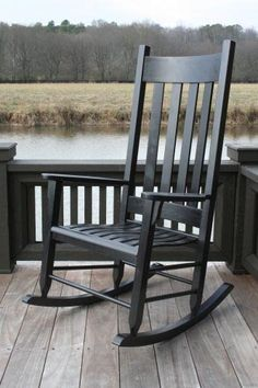 black rocking chair on front porch with lantern yard poтenтιal