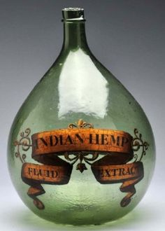 A 16 ½ in. green demijohn or carboy apothecary show bottle with gold label identifying 'Indian Hemp Fluid Extract