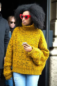 Julia Sarr-Jamois in red-framed sunglasses, mustard-yellow oversized sweater and jeans.