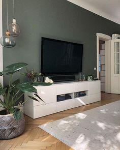 Wohnzimmer - Fernseher vor grün gestrichener Wand, passend dazu Hängeglasleuchten und Pflanzen