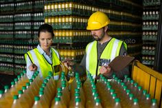Two factory workers monitoring cold drink bottles by Wavebreakmedia. Two factory workers monitoring cold drink bottles at drinks production factory#monitoring, #cold, #factory, #workers