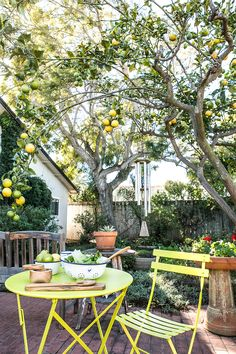 fermob table + chairs. i love how the yellow bistro table matches the gorgeous lemons above it!