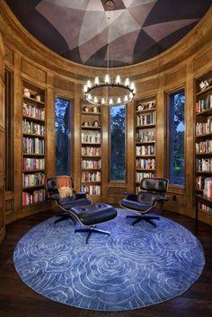 Geometric shapes command the dome. A circular light fixture illumines four bookshelves separated by tall vertical windows. JAUREGUI Architecture Interiors Construction. Austin, TX.