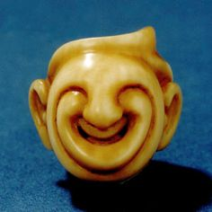 Ojime, the small companions of netsuke. They are beads which slide along the two cords that run between the netsuke and the object it is suspending. The ojime slides down toward the top of the bag or lacquer box and thus stops them from accidentally opening. Ojime are carved in the round, but are much smaller than netsuke with their size usually ranging from around 1-2cm. In contemporary times they are often used as pendants.Leigh Sloggett