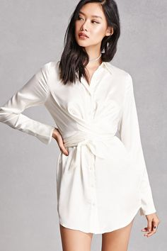 A satin shirt featuring a self-tie belt, a button and wrap front, basic collar, long sleeves with button cuffs, and a pleated back. This is an independent brand and not a Forever 21 branded item.