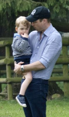 Doting father Prince William holds Prince George in his arms during their day at the famous stately home