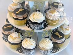 Variety of cupcakes for a 50th birthday celebration with glitter cardstock and fondant toppers including stars and wine glasses in a colour scheme of black, white, and gold. Chocolate cupcakes, chocolate truffle filling, coffee or vanilla buttercream; vanilla cupcakes, maple cream cheese filling, cinnamon or cream cheese flavour buttercream.