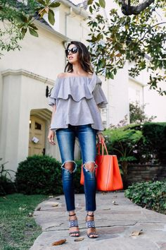 A ruffle front off the shoulder top, ripped jeans, sandals, and a poppy red tote.