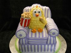 "This cake was for my brother in law. He has a slightly twisted sense of humor. When I asked him what kind of birthday cake he wanted, he paused, started laughing and said, "" I want a chicken eating a bucket of fried chicken!""  This is what I came up with.  Lemon cake with raspberry filling. Part of the chair and the chicken are made with RKT."