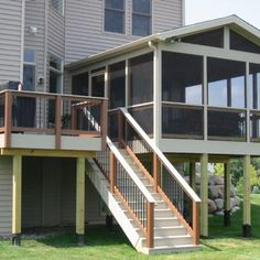 This second story screened porch features composite decking and railings, and black Deckorator aluminum balusters.This lovely elevated Durham screened in porch and deck combo presented a specific challenge. With the special architectural bend in the back of this home, building a porch and deck that fit in took some design work that Archadeck of Raleigh-Durham loves to tackle head on. The open gable roof and wide screen openings make this a perfect open airy porch. The grill deck fit…