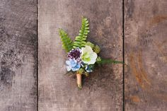 For spring's lush forest weddings, design a boutonniere that reflects your natural surroundings. This enchanting rustic example features green berries and ferns behind a couple of sweet blooms.