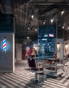 The illuminated red, white, and blue pole pays tribute to a barber shop mainstay. To nod at the desired throw-back vibe, Sadiku's design team, Kevin Chan and Samer Shaath, co-founders of Toronto's Nivek Remas, lined the entire ceiling, as opposed to the walls, with ornamental plaster work. Likewise, the floor, an inlaid zigzag of two-toned grey tiles, also twists tradition. #InteriorDesign #RetailSpaces #RetailDesign