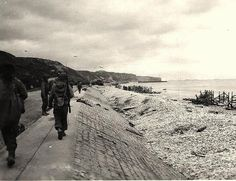 American soldiers walking along road towards western end of Omaha Beach. Vierville-sur-Mer - Dog White sector, Omaha Beach, D-Day +1