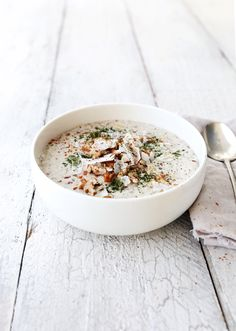 nutty paleo porridge topped with coconut flakes, pecans, cinnamon and super greens powder