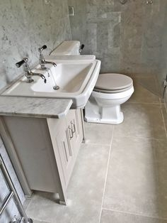 Paris Grey limestone and Carrara marble tiles were used on the floors and walls in this compact yet beautiful bathroom.  Bathroom tile ideas. http://www.naturalstoneconsulting.co.uk/stone-tiles-flooring.php