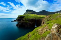 Village of Gasadalur overlooked by Heinanova mountain, with waterfall cascading over cliff into the Atlantic Ocean.