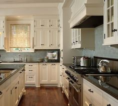Perfect kitchen color scheme. Dark granite and cream cabinets with light blue subway tile.