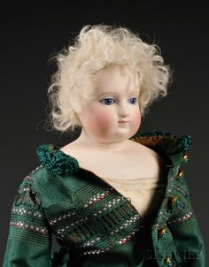 Early Shoulder Head French Fashion Doll, France, c. 1870, possibly Huret, cobalt blue stationary eyes, closed mouth, new skin wig over cork pate, shoulder head on gusseted kid body, marked in green block letters on chest HURET, new green dress, ht. 16 in.