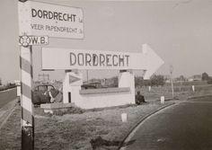 Anonymous | ANWB bord: Dordrecht, Anonymous, 1941 - 1942 | Langs een autoweg staat een ANWB bord richting Dordrecht. Daarnaast een constructie van steen met een pijl die het opschrift bevat: Dordrecht. Eronder een driehoek met vliegende vogel. Verwijzing naar Luftwaffe basis? Tegen de constructie leunt een Duitse militair. Erachter staan twee auto's met een blond jongetje.