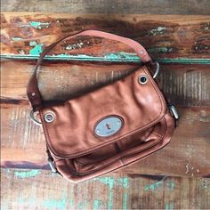 """Fossil leather purse Over the shoulder light brown leather purse. Magnetic closure for front flap and pocket in the back. Clean interior, but broken zipper on inside pocket. Overall there is wear on the leather (fading). Missing two metal caps (see pic 4). One of the metal thingys missing is on back as shown and the other was on side. Approx 11"""" long, 7.5"""" tall, and 2"""" at widest. Strap drop 8"""" Fossil Bags Shoulder Bags"""