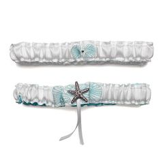 Seaside Allure Bridal Garter Set includes a keepsake and a toss garter. Both garters feature an elastic band covered in white satin. The toss garter is embroidered in blue with a starfish design and a rhinestone. The keepsake garter is embroidered in blue with a seashell design and then decorated with a sparkling starfish charm and two white satin streamers.
