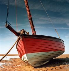 Red sailing boat moored at Meols, Wirral coast. Clinker built dinghy