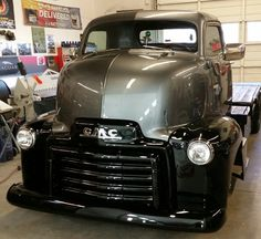 GMC COE in gray and black gloss finish with a sweet flat bed on the back.