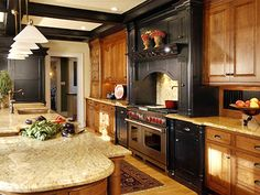 Kitchen Design Inspirations: The distressed black cabinetry surrounding the range is a commanding focal point in this Americana-styled kitchen. The coffered ceiling is used to tie the entire room together. Design by Dave Stimmel. From DIYnetwork.com