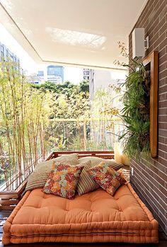 Nesta varanda, o tatame, feito de deque de cumaru, recebe o futon e as almofadas para compor o espaço destinado ao descanso