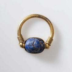 Scarab ring of Shoshenq III--Egyptian, Third Intermediate Period, Dynasty 22, reign of, 825–773 B.C.; Solid gold ring (round band) with lapis lazuli scarab. Scarab held in narrow gold band. Wire running through scarab wrapped round ring several times at either end of ring.