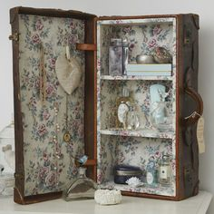 Vintage bathroom storage Create your own display cabinet for perfume bottles by lining a small vintage suitcase with pretty wall paper. The underside of the lid can be used to hang up jewelry and keepsakes.