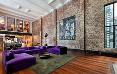 Beautiful hardwood flooring against brick walls and white ceilings. That purple couch is killer.