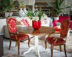 mesa com tampo escuro e pe branco, com cadeiras vermelhas.