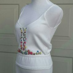 "Moda International White Embroidered Knit Camisole Pretty white knit tank with embroidered flowers running down the sides of the 6 buttons down the front. Chest 16"" flat, length from top of straps 20"". Cotton acrylic blend. Ultra soft and so feminine Moda International Tops Camisoles"