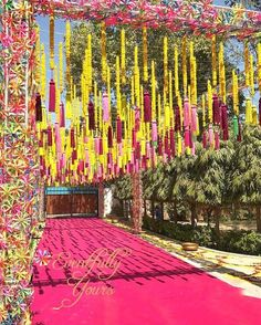 Kitschy and fun wedding decor | Hanging marigold flower chains with tassel ends | Handing tassels | Pink decor | gate adorned with pinwheels | Quirky mehendi decor inspiration | Indian wedding decor | Styled by Eventfully yours | Every Indian bride's Fav. Wedding E-magazine to read. Here for any marriage advice you need | www.wittyvows.com shares things no one tells brides, covers real weddings, ideas, inspirations, design trends and the right vendors, candid photographers etc.