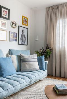 Sala de estar tem sofá azul claro e parede galeria.