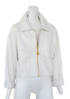 www.resurrectionvintage.com Chanel White leather cropped swing jacket with classic Chanel quilt detail on collar, over sized patch pockets and rolled cuff. It sports a relaxed shoulder and a gold zipper closure with Chanel charm zipper pull.
