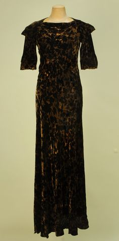 Front View VOIDED VELVET and GOLD BIAS CUT EVENING GOWN, c. 1930. Black velvet in an overall pattern of cherries on a metallic gold ground with draped cutout V-back with four self button and loop closures at top, slight cowl front, pointed cap sleeve and unusual looped arm treatment.