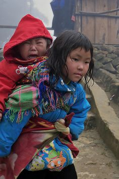 Vietnam - little brother on his sister's back.