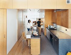 "In the kitchen, the architects contrasted the oak floor, bamboo cabinetry, and birch walls and ceiling with what architect Jonathan Knowles calls ""a family of grays"": granite floor tiles, limestone countertops, and the steel stairway. The birch wall behind Yvette is actually the sliding door to the pantry closet. Photo by: Adam Friedberg Read more: http://www.dwell.com/slideshows/harlem-renaissance.html?slide=3=y=true##ixzz25i7mc7Bw"