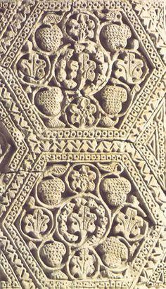 """Estuco decorativo. Samarra (Irak), siglo IX. Es la técnica más utilizada para la decoración de los palacios abasíes. El de la foto está inspirado en la viña, con hojas y racimos inscritas en un exágono (Museo de Bagdad). Se corresponde con """"el estilo A"""" descrito por los especialistas Herzfeld y Creswell."""