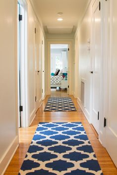 Cobalt-blue Moroccan-inspired rugs line this transitional hallway, adding color and style to the neutral space. The rugs also help to soften the hardwood floors, ensuring the space feels inviting and homey.