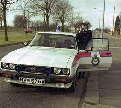 A Greater Manchester Police officer and her Ford Capri vehicle in… Manchester Police, London Police, Ford Police, Police Officer, British Police Cars, Emergency Vehicles, Police Vehicles, Police Uniforms, Ford Capri