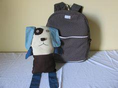 Mochila em tecido com dois bolsos externos laterais, acompanha também um cachorrinho estilo naninha, que quando retirado da mochila vira um lindo brinquedo <br>Ideal para o dia a dia, saídas rápidas, para levar a escola e passeios <br>Ótimo espaço interno e pode ser utilizado também pela mamãe, que com as mãos livres pode segurar com segurança seu bebê <br> <br>Tecido tricoline 100% algodão <br>Estruturada com manta resinada que deixa a mochila estabilizada <br>Contém dois bolsos externos e…