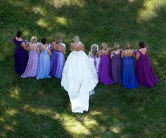 Bridesmaids in shades of purple and blue make the bride's embellished ball gown pop.