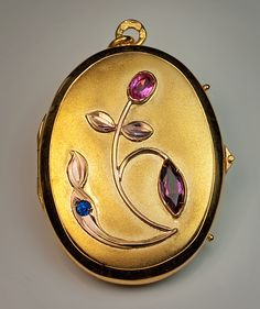 An Antique Russian Jeweled Gold Locket, made in Odessa 1908 - 1917. The cover of this 14K yellow gold locket has a matte finish and a contrasting polished border. The locket is embellished with an Art Nouveau jeweled rose gold flower. The flower is set with pink and blue synthetic sapphires and a marquise cut rhodolite garnet.