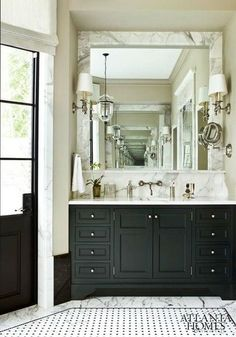 Very handsome and quite masculine black and cream bathroom in Atlanta. Love the black and white vintage tile surrounded by Carrara marble, and well as the same marble framing the mirror. Great wall-mounted sink, sconces, and pendant lantern. And, of cours...