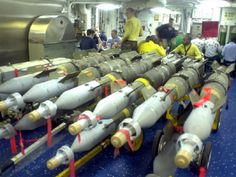 At sea aboard USS Enterprise, Oct. 11, 2001 — Sailors aboard USS Enterprise (CVN 65) take a break from the business of the day for meals and relaxation. However, never far away are reminders of the serious mission supported by every member of the crew. Bombs stand ready on the mess decks, prior to their transfer to the flight deck above, for missions over Afghanistan in support of Operation Enduring Freedom.