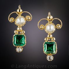 A bright and lively pair of old-mine square-cut emeralds, totaling 1.25 carats but presenting considerably larger, glisten from within gracefully decorative 18K yellow gold settings. The two emeralds are surmounted by lustrous natural button pearls centering finely milgrained scrolls with antique cushion-cut diamonds sparkling at the bottoms. Extremely lovely and far-from-ordinary antique earrings with an artsy, antiquarian flair.