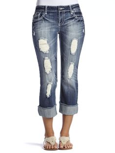 """Our favorite Dakota regular fit fashion crop jean fits slightly in the hip, thigh and knee. Contrast white thick stitch, crystal buttons, heavy destruction, frayed cuff and signature wavy """"V"""" on back pockets finish off the look to keep you in style. Imported."""